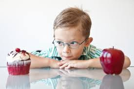 Boy choosing from an apple or a cupcake symbolic to choose between the right consultant